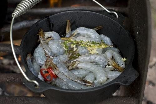 Cooking garlic prawns in a camp oven