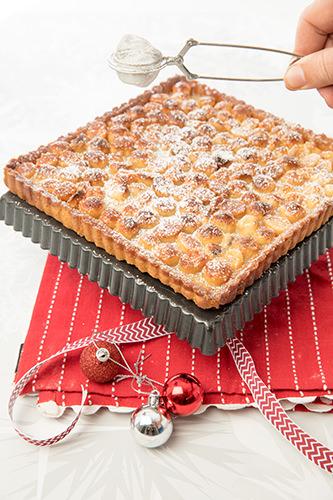 Dusting the Macadamia & Caramel Tart with icing sugar
